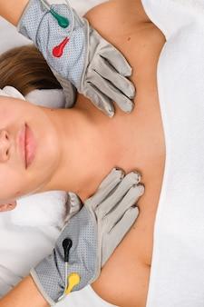 Cosmétologue matériel dans des gants à microcourant gris pour la thérapie de myostimulation