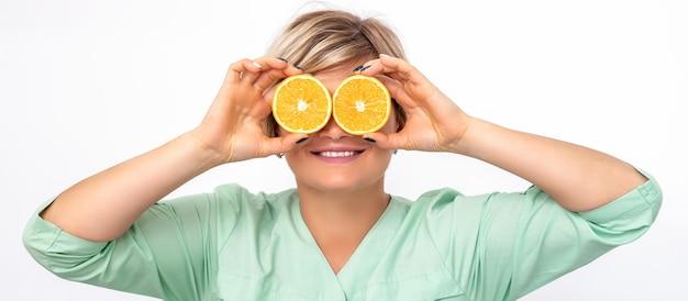 Cosmétologue ou nutritionniste couvrant les yeux avec deux moitiés de fruits orange sur fond blanc
