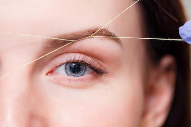 Cosmétologue plume les sourcils des clients par fil