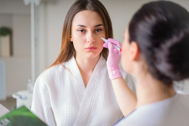 Cosmétologue prêt à peindre des lignes avec un marqueur sur le visage du patient