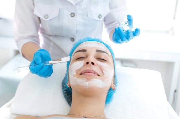 Un cosmétologue professionnel applique une crème nourrissante sur le visage du patient