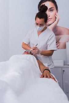 Cosmétologue professionnel effectuant une procédure de mésothérapie avec dermapen à une femme adulte