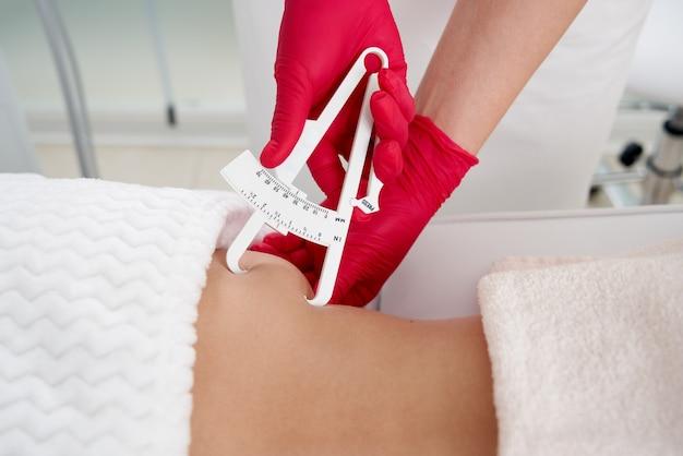 Cosmétologue utilisant un pied à coulisse pour mesurer la graisse corporelle sur la ligne de taille du régime alimentaire du patient et de la perte de poids