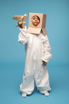 Cosmonaute drôle mignon en vêtements blancs et boîte en carton sur sa tête en gardant la main droite par le temple tout en jouant dans le salon
