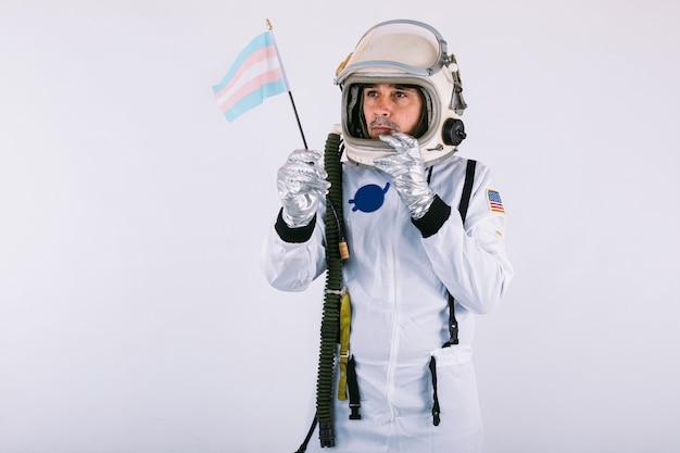 Cosmonaute masculin transsexuel gay avec un geste sérieux en combinaison spatiale et casque, tenant le drapeau transgenre, sur fond blanc.