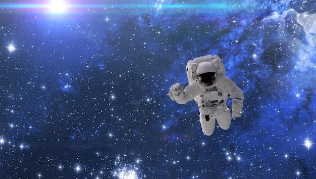 Un cosmonaute vole dans l'espace avec des étoiles et un fond de galaxie avec un faisceau lumineux. éléments de cette image fournis par la nasa