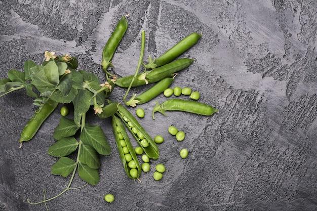 Cosses de pois verts avec des feuilles sur table loft gris