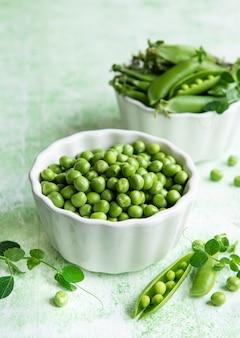 Cosses de pois verts frais et pois verts avec pousses sur fond de bois vert. concept d'alimentation saine, légumes frais.