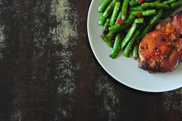 Cosses de pois verts et steak de porc sur une assiette. régime céto.