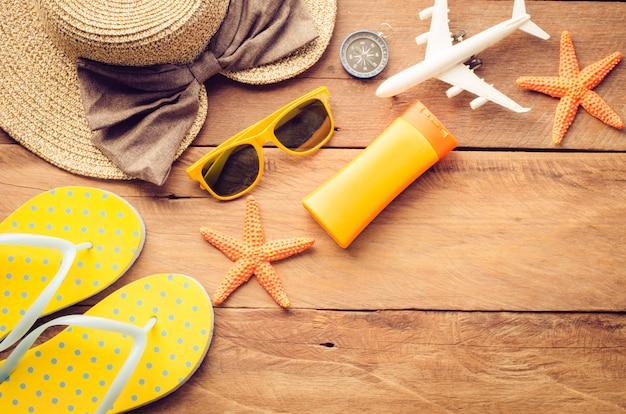Costume d'accessoires avec voyage pour l'été sur le plancher en bois