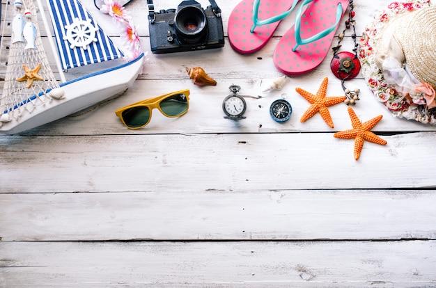 Costume d'accessoires avec un voyage pour l'été sur un plancher en bois