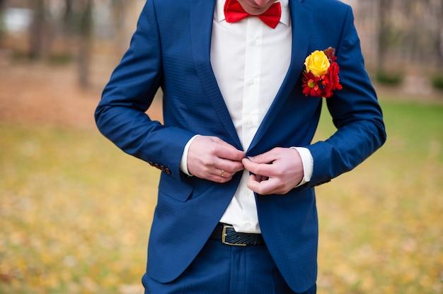 Costume bleu bouton de marié.