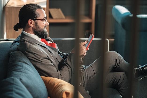Costume cravate. homme barbu portant un costume gris et une cravate rouge tenant son message de lecture de téléphone