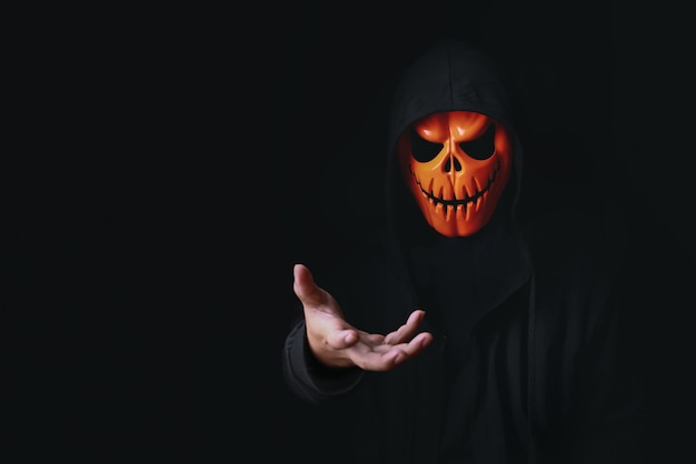 Costume de diable d'horreur avec crâne de citrouille effrayant en noir habillé pour le carnaval d'halloween
