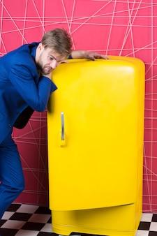 Un costume élégant formel pour homme se tient près d'un réfrigérateur jaune vintage rétro. appareils électroménagers d'époque. le célibataire affamé pense à quoi manger près du réfrigérateur. appareils électroménagers de réfrigérateur lumineux. faim et appétit.