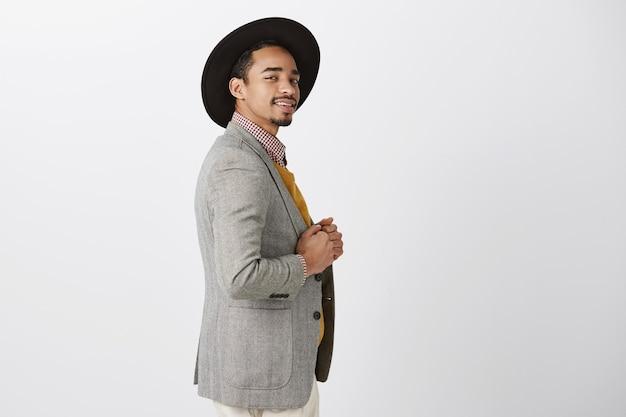 Le costume fait que le gars ressemble à un vrai gentleman. portrait d'homme attrayant heureux debout de profil, souriant avec confiance, tenant les mains sur le manteau, se sentir élégant