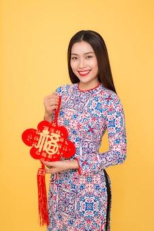 Costume de festival traditionnel de femme vietnamienne ao dai tenant des attributs. texte signifie bonheur.