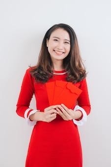 Costume de fête traditionnelle vietnamienne ao dai, tenant des poches d'argent rouge.