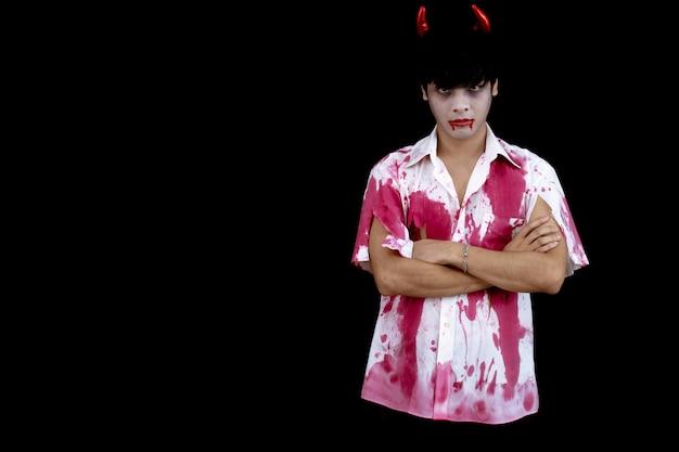 Costume de jeune homme asiatique en enfer, mal sur fond noir avec concept pour le festival de la mode halloween en studio. teen asiatique homme en cosplay halloween.