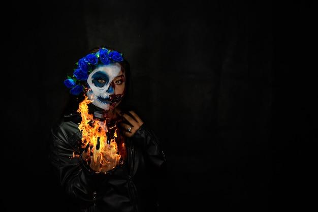 Costume et maquillage d'halloween portrait de catrina aux mains de feu