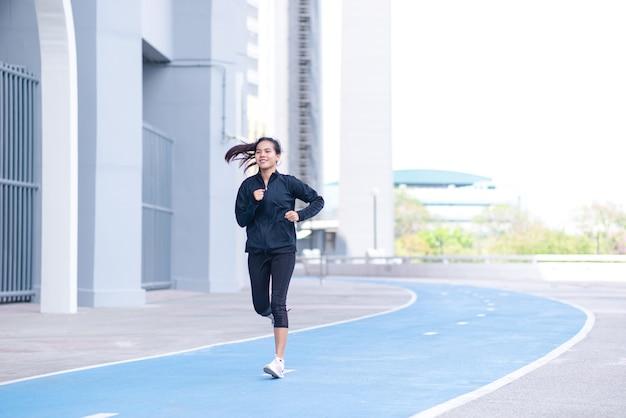 Costume noir de belle jeune femme asiatique avec la course heureuse ou le jogging sur la piste de course.