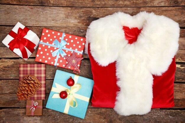 Costume de père noël avec des coffrets cadeaux sur fond de bois, gros plan