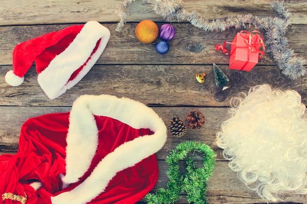 Costume de père noël, petit arbre, pomme de pin, boules de noël, guirlande, cadeau sur fond en bois