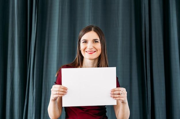 Costume rouge fille tient un morceau de papier, fond, enregistrement, lettrage sur la feuille, la base du texte, fond blanc, publicité