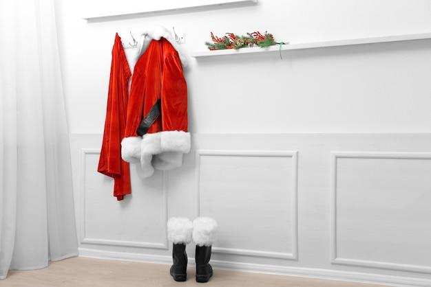 Costume de santa accroché sur fond de mur blanc