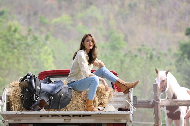 Un costume de tenue de cow-girl femme assis sur un camion contre un cheval dans une ferme d'élevage.