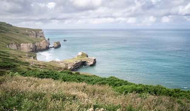 Côte aux eaux turquoise de l'océan et falaises de grès de formes diverses plage tunnel nouvelle-zélande