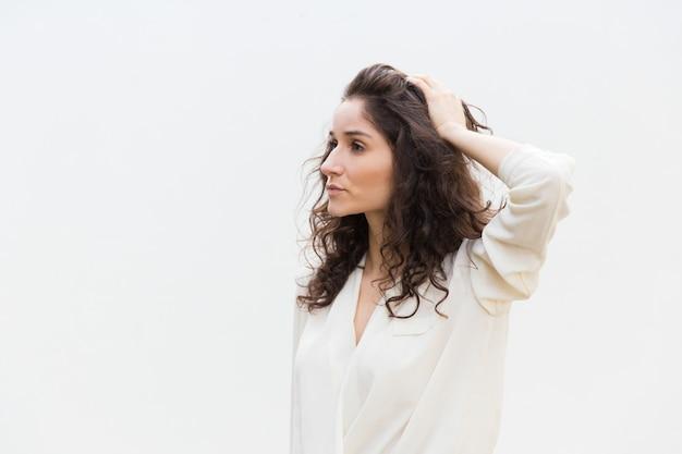 Côté de la belle femme sérieuse pensive touchant les cheveux