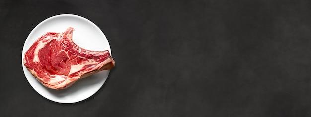 Côte de boeuf crue et assiette isolée sur fond de béton noir. vue de dessus. bannière horizontale