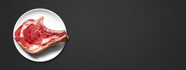 Côte de boeuf crue et assiette isolée sur fond noir. vue de dessus. bannière horizontale