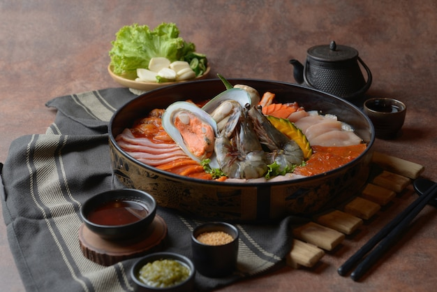 Côte de bœuf garnie de sésame et fruits de mer avec crevettes disposées sur le plateau et légumes pour un grill posé sur la table.