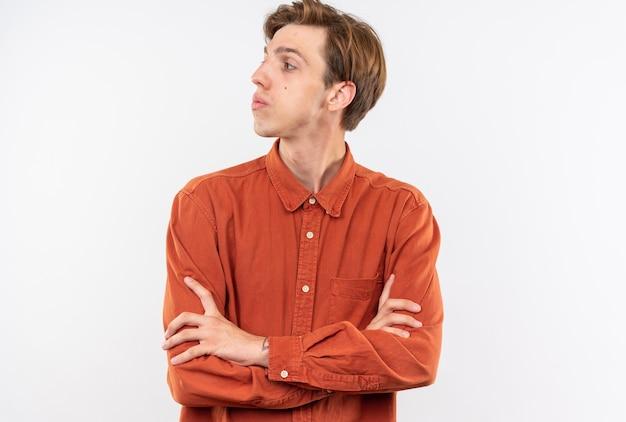 Côté confiant à la recherche d'un jeune beau mec vêtu d'une chemise rouge croisant les mains isolées sur un mur blanc