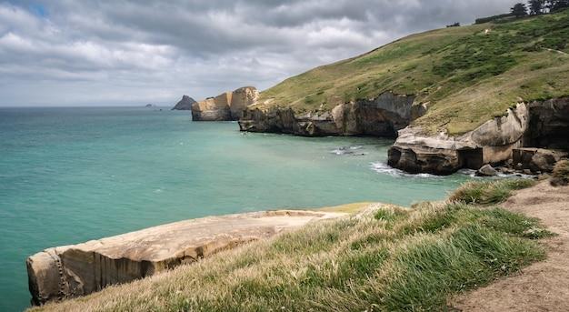 Côte avec des falaises de grès sur l'image de jour tunnel beach dunedin péninsule d'otago en nouvelle-zélande