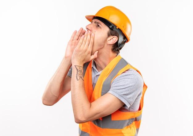 À côté de l'homme jeune constructeur en uniforme appelant quelqu'un isolé sur mur blanc