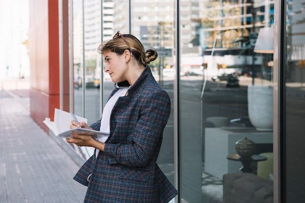 Côté jeune femme d'affaires écrivant dans le cahier avec un stylo