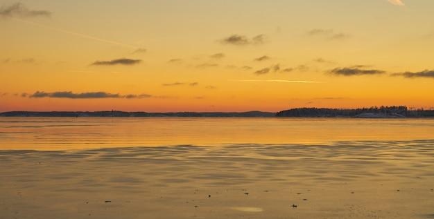 La côte de la mer dans la glace et dans la neige au coucher du soleil