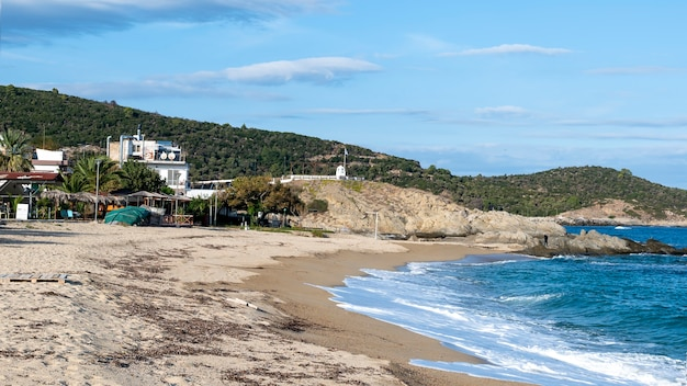 Côte de la mer égée avec des bâtiments sur la gauche, des rochers, des buissons et des arbres, de l'eau bleue avec des vagues à sarti, grèce