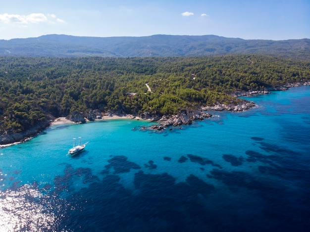 Côte de la mer égée avec de l'eau transparente bleue et bateau, verdure autour, rochers, buissons et arbres, vue depuis le drone, grèce