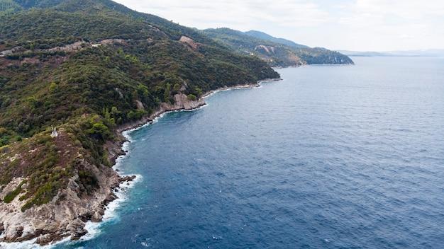Côte de la mer égée avec eau transparente bleue, verdure autour, rochers, buissons et arbres, vue depuis le drone grèce
