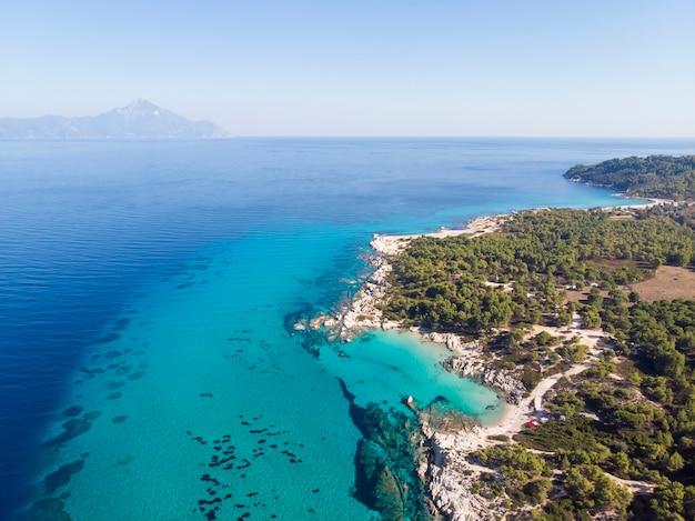 Côte de la mer égée avec de l'eau transparente bleue, verdure autour, rochers, buissons et arbres, vue depuis le drone, montagne grèce
