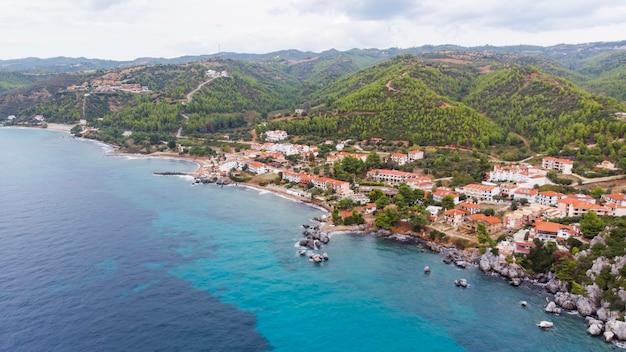 Côte de la mer égée de la grèce, bâtiments loutra situés près des falaises rocheuses, de la verdure et de l'eau bleue. vue depuis le drone
