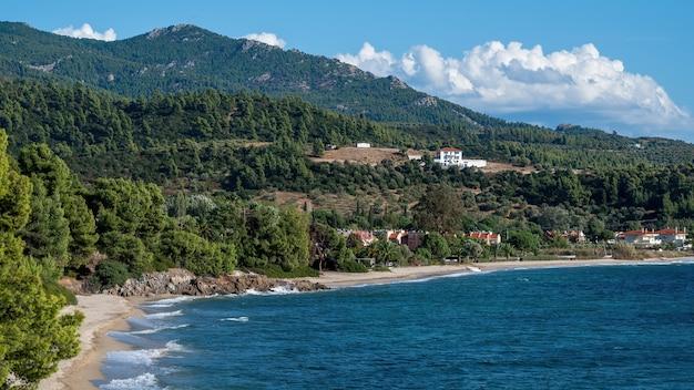 Côte de la mer égée de la grèce, collines rocheuses avec des arbres et des buissons en croissance, des bâtiments situés près de la côte
