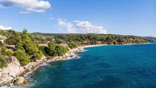 Côte de la mer égée de la grèce, collines rocheuses avec des arbres et des buissons en croissance, grande étendue d'eau