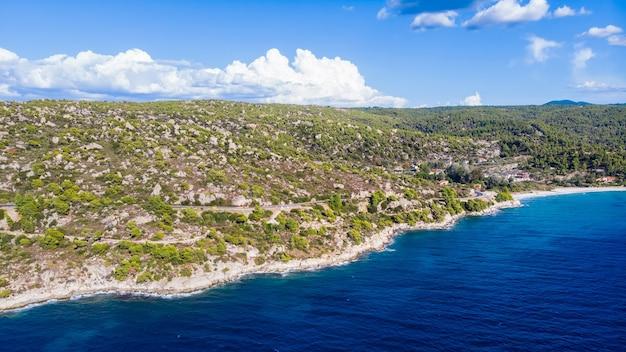 Côte de la mer égée de la grèce, collines rocheuses avec des arbres et des buissons en croissance, quelques bâtiments près du rivage