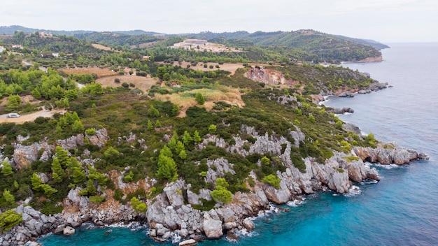 Côte de la mer égée de la grèce, falaises rocheuses, verdure et eau bleue. vue depuis le drone