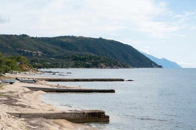 Côte de la mer égée à ouranoupolis avec des bateaux échoués et trois vieux quais en grèce